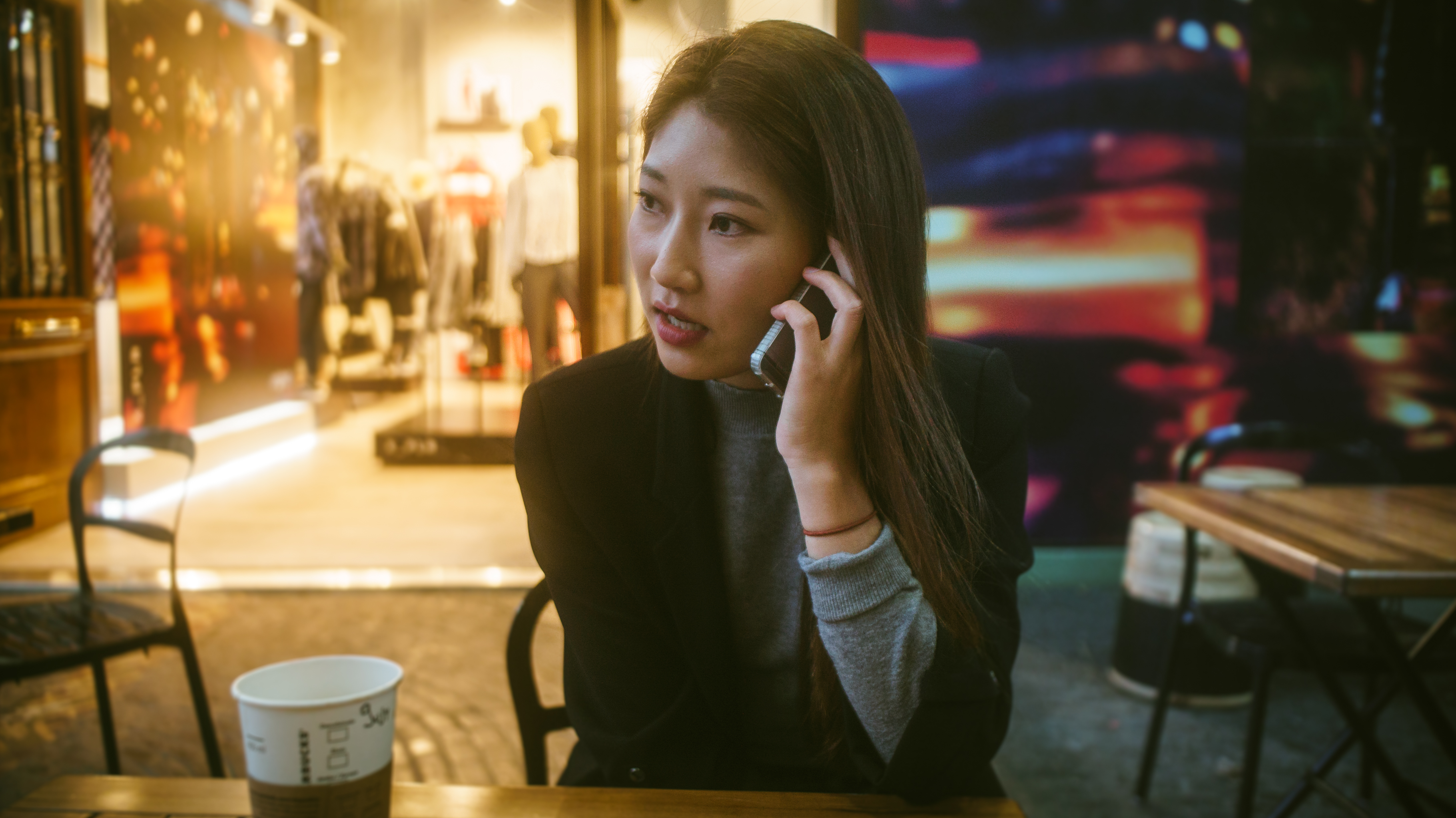 woman talking on phone outdoor in front of store