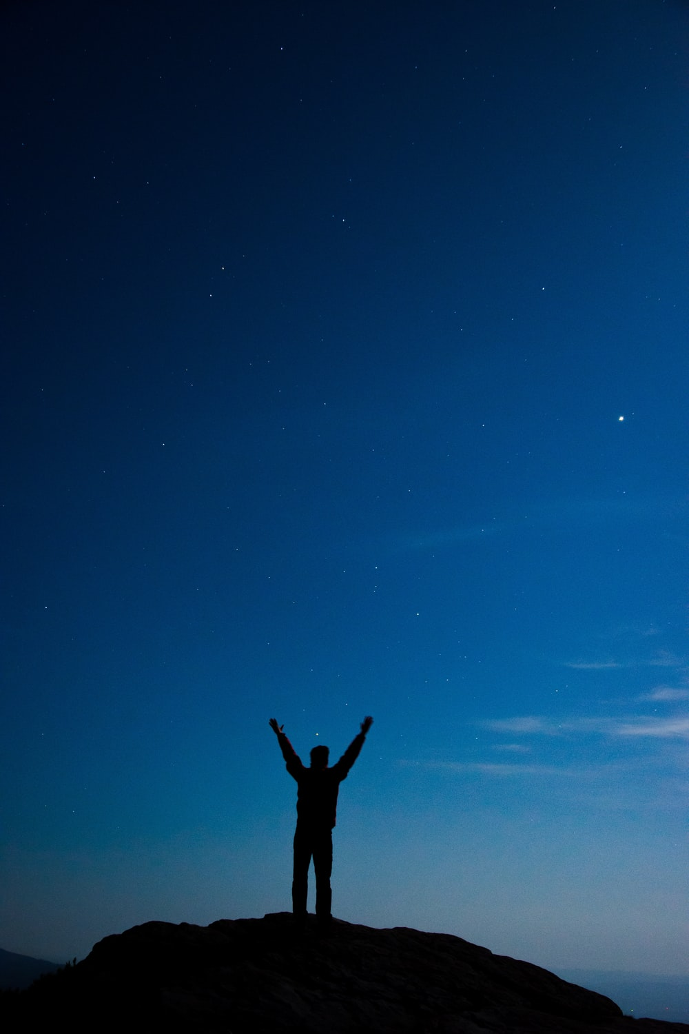 silhouette of man standing on hill with arms wide open