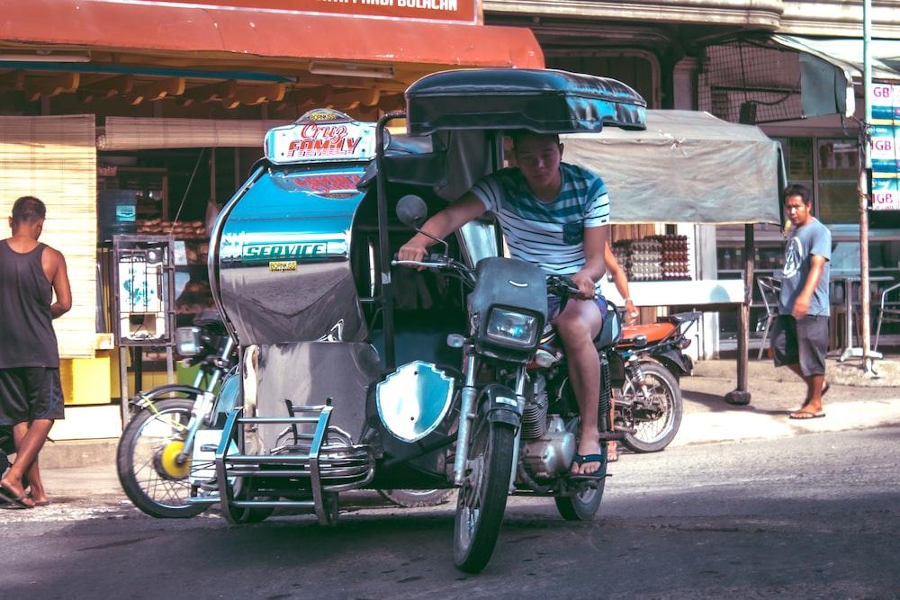 man riding tricycle during daytime