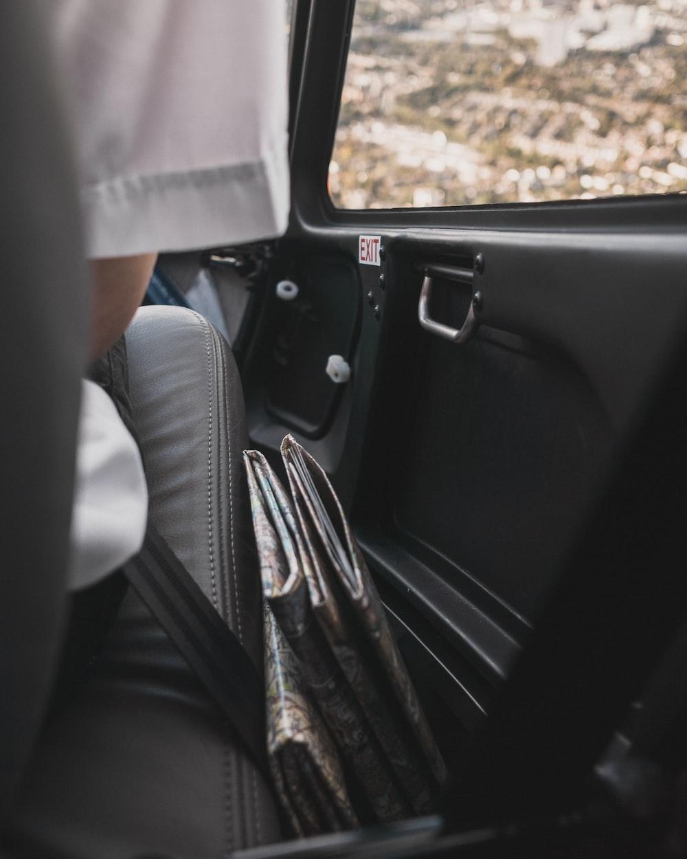 person sitting inside car beside door\