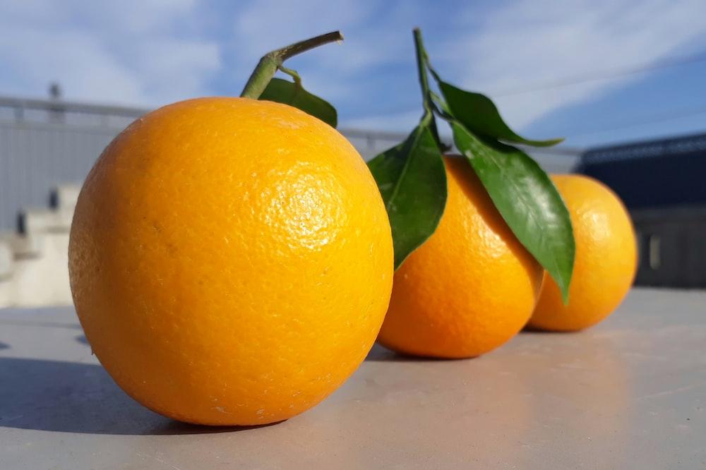 three round orange fruits on gray table