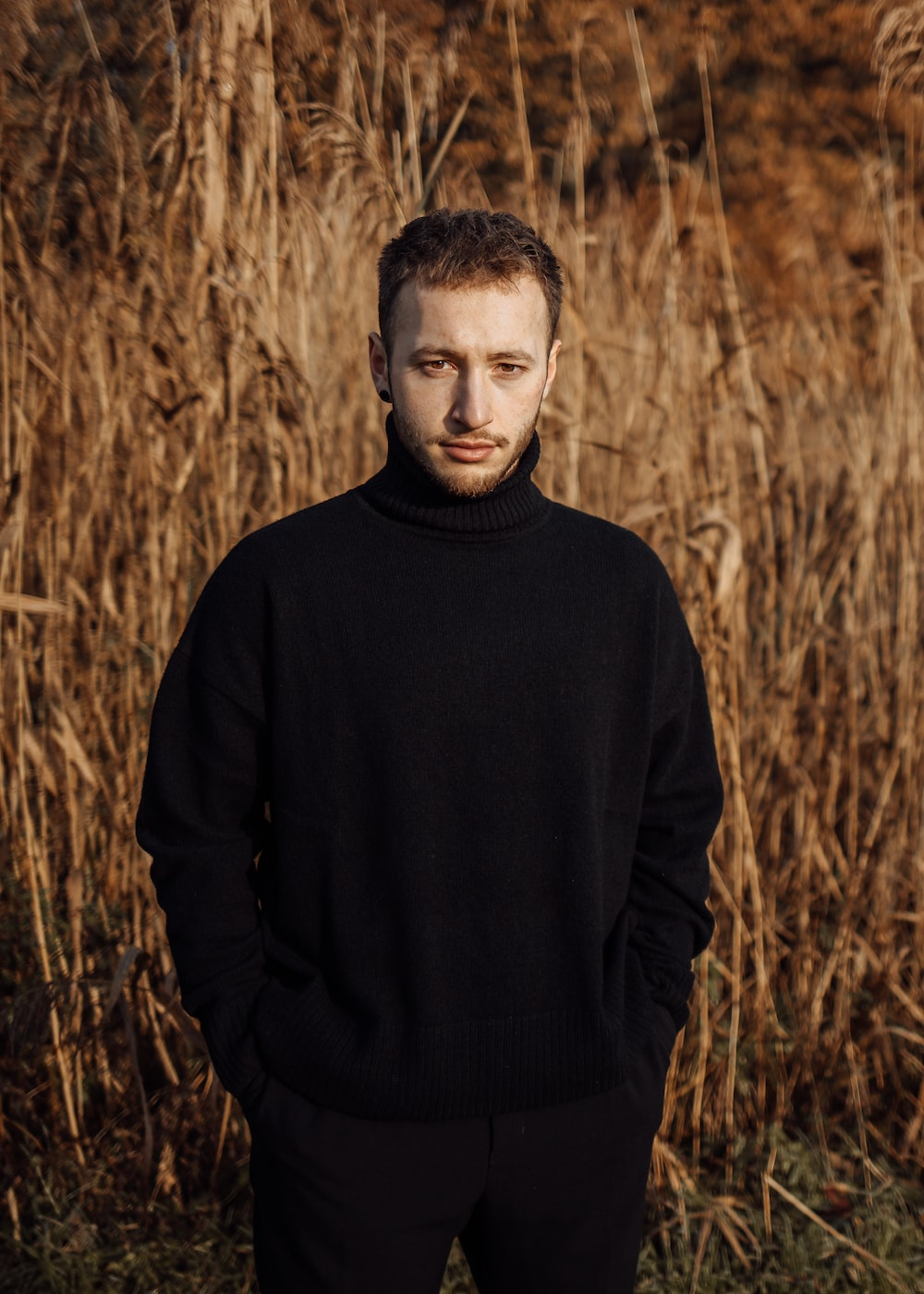 man in black turtleneck sweater by plant field during daytime