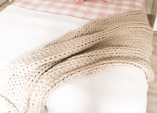 brown knitted blanket on bed with pillows
