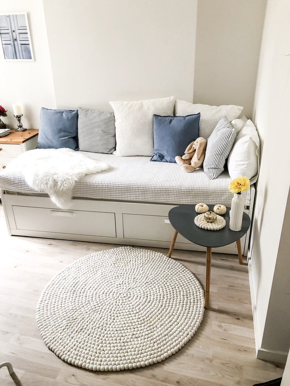 blue and white pillows on white couch and round white area mat on floor