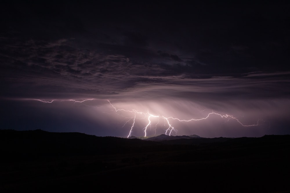 silhouette photography of mountain and lightning bolt
