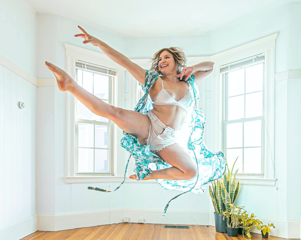 woman wearing blue cardigan jumping