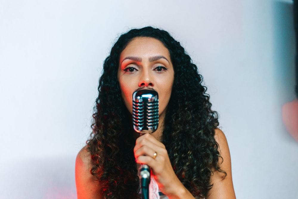 woman singing using condenser microphone