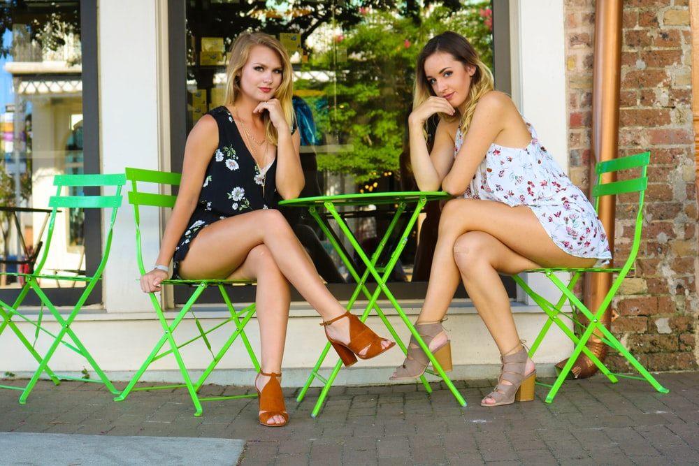 two women sitting on green chairs leaning on round green table