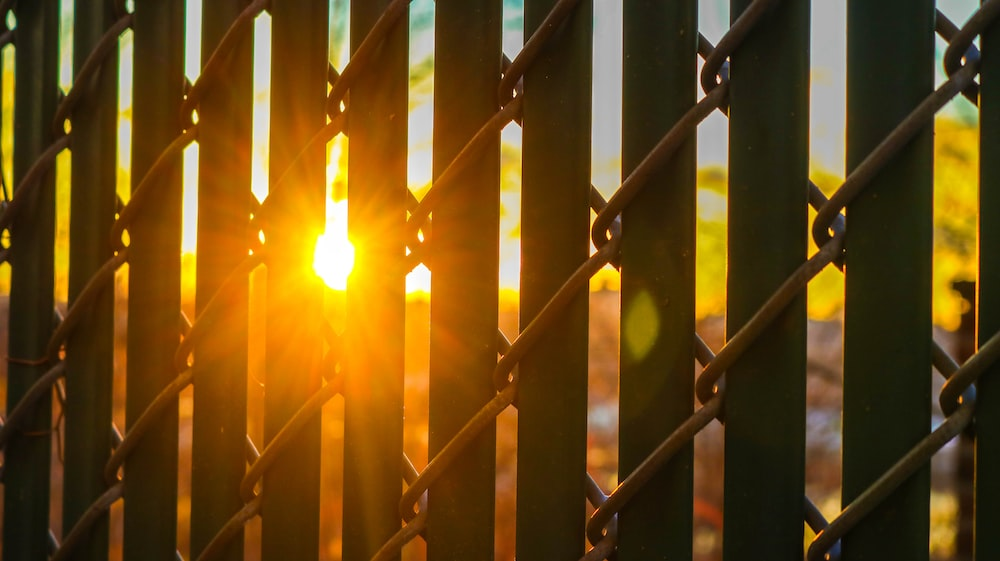 black grill with link fence against the sun