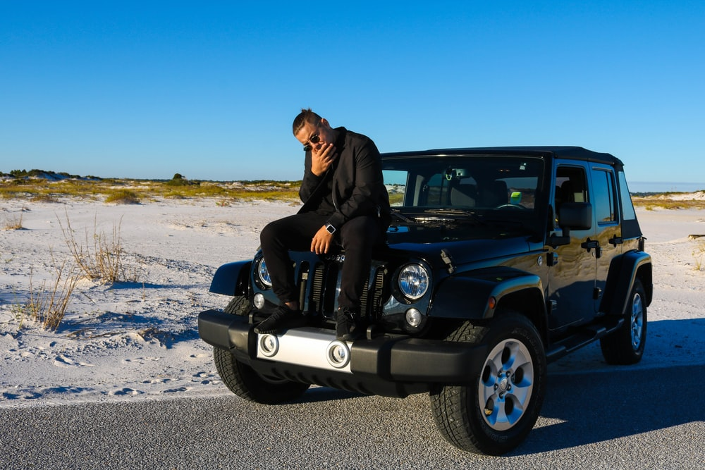 photography of man sits on vehicle during daytime