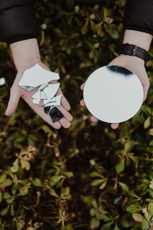 person holding round mirror