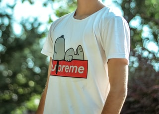 man wearing white and red Supreme crew-neck shirt