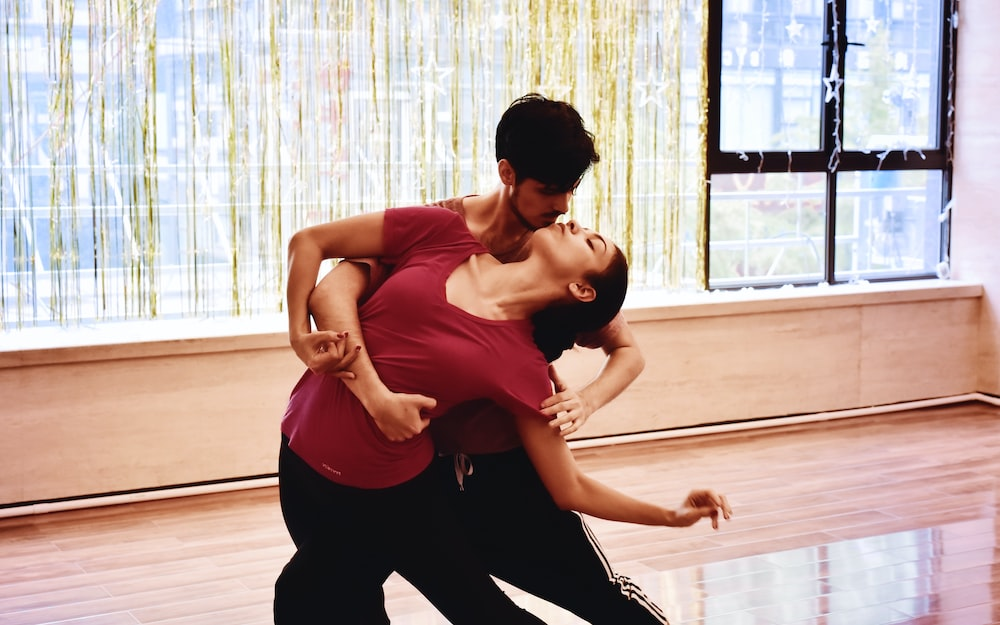 photography of dancing man and woman inside room