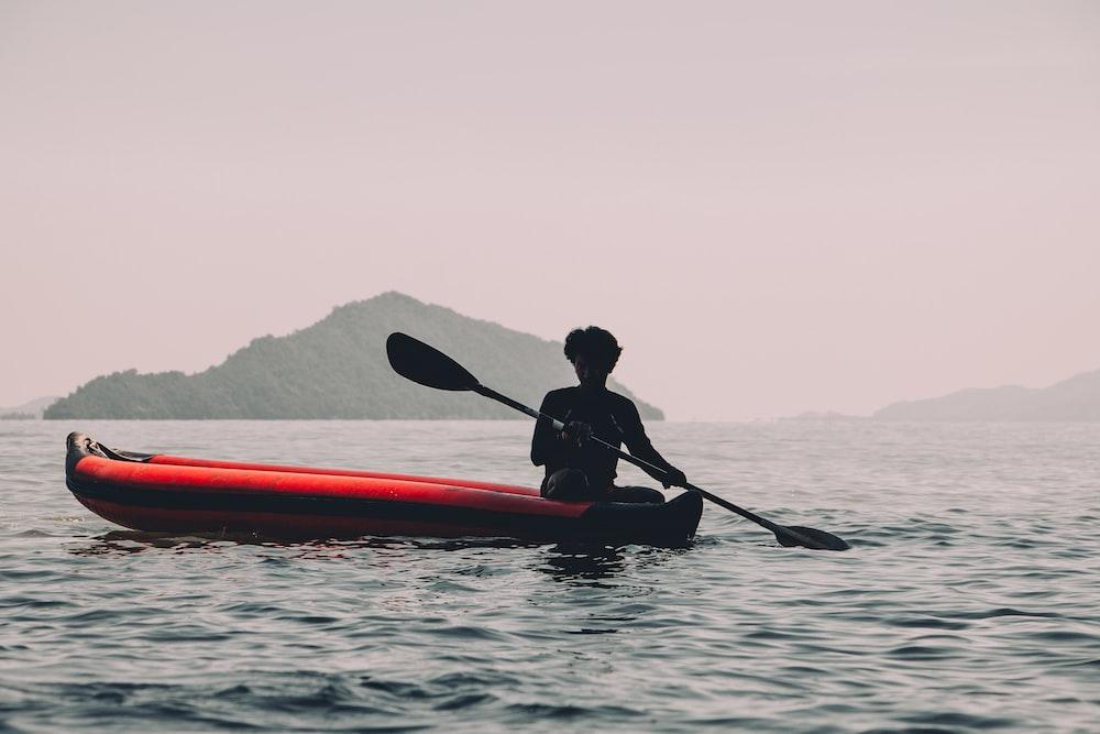 person riding red kayak
