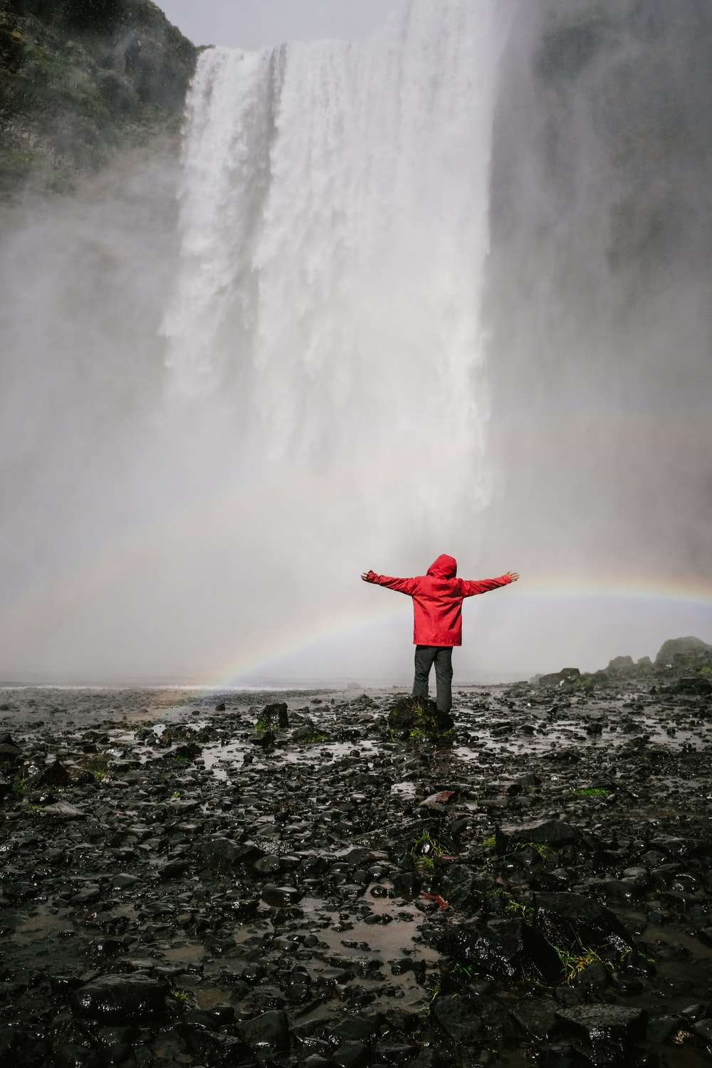 person standing infront of waterfalls
