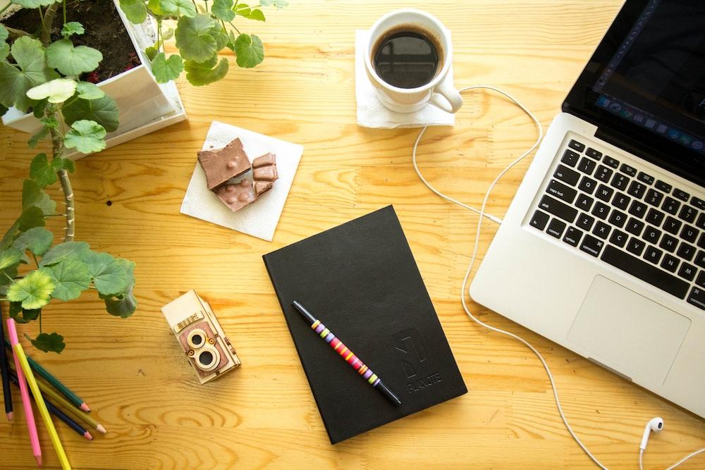 MacBook Pro beside cup of coffee