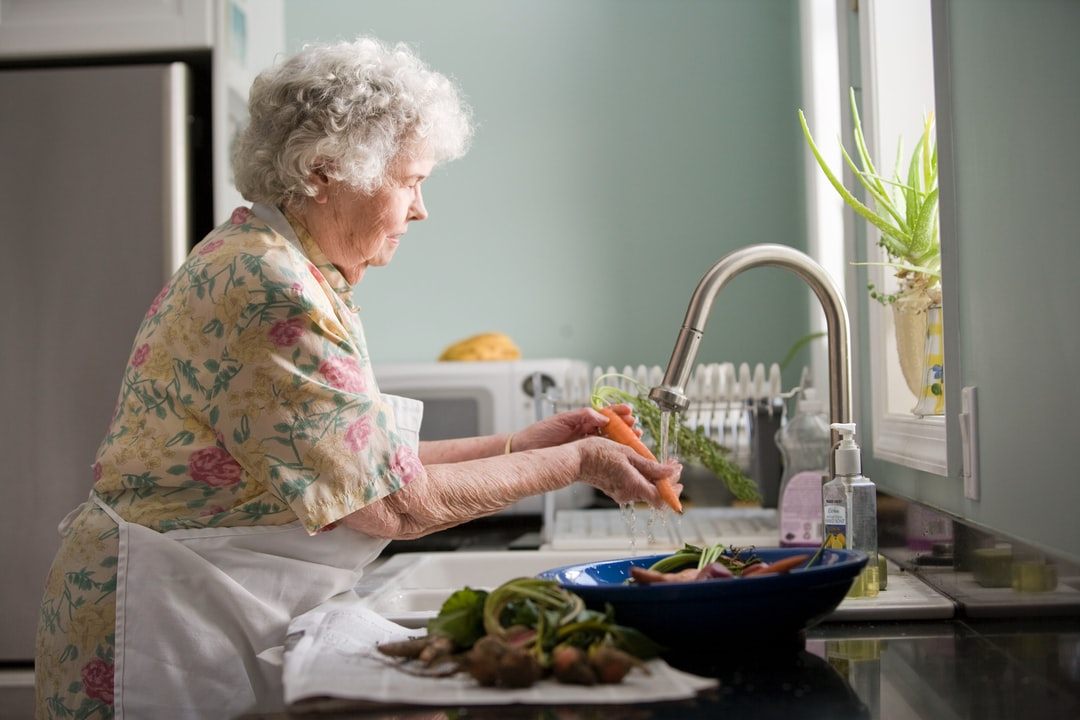 Elderly woman cleaning vegetables. Photo by Cade Martin