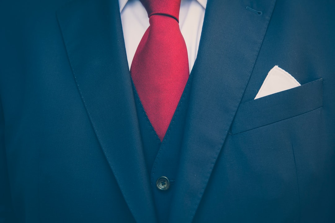 Business men with darkblue suit, vest and red tie