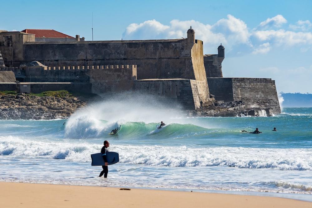 people surfboarding on beach near fort