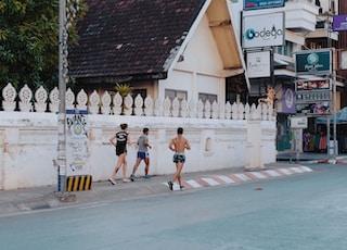 three men jogging on sidewalk