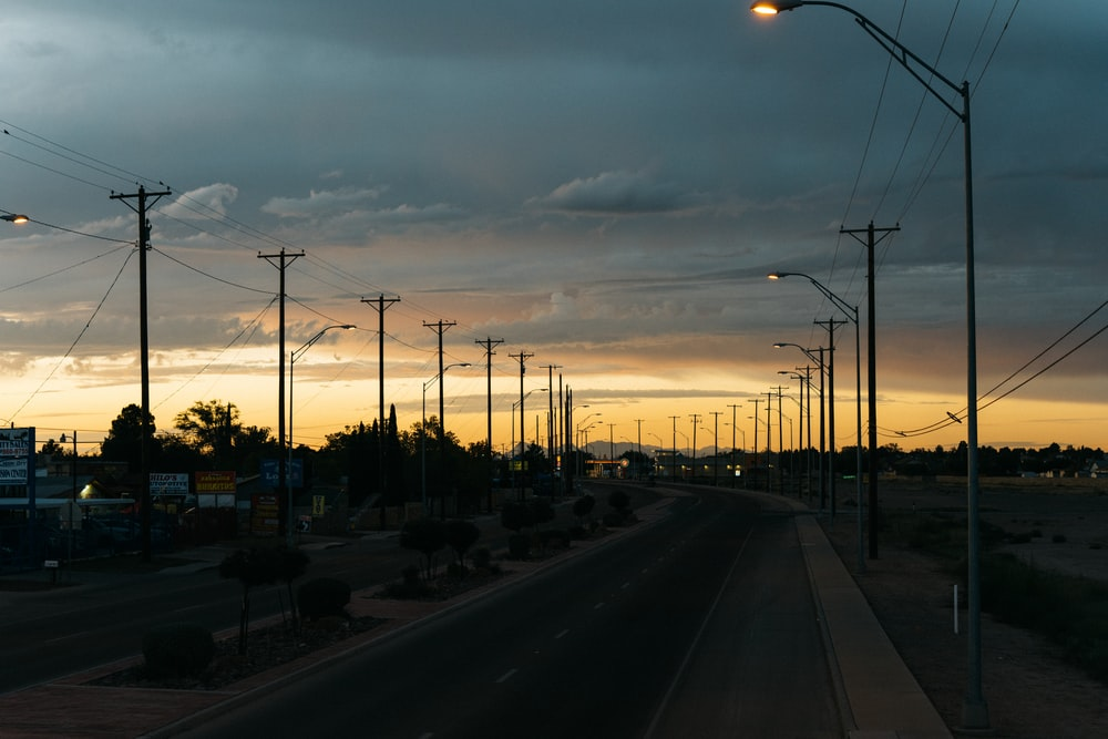 empty road with turned on lights under white skies during golden hour