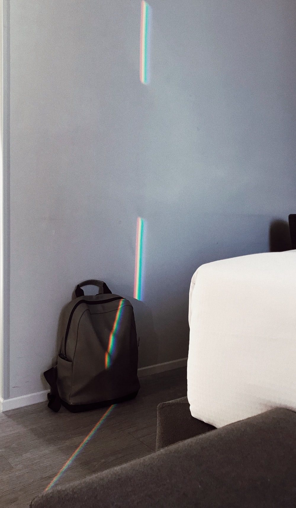 gray backpack beside wall