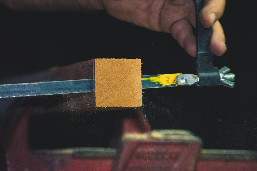 person sawing timber