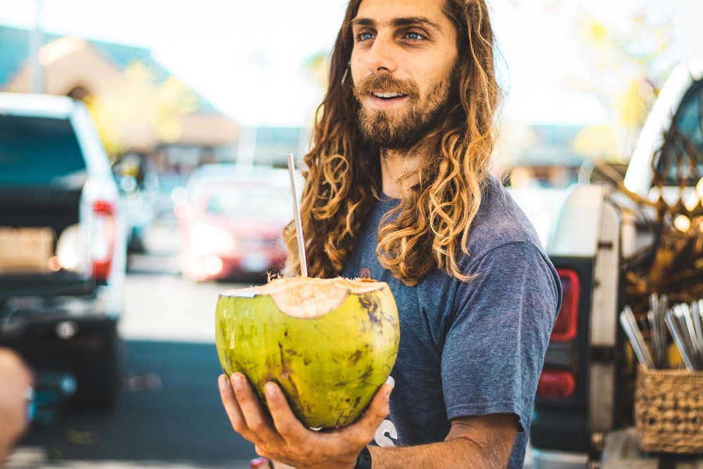 man holding coconut fruit