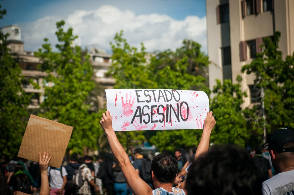 man holding signage displaying estado asesino text