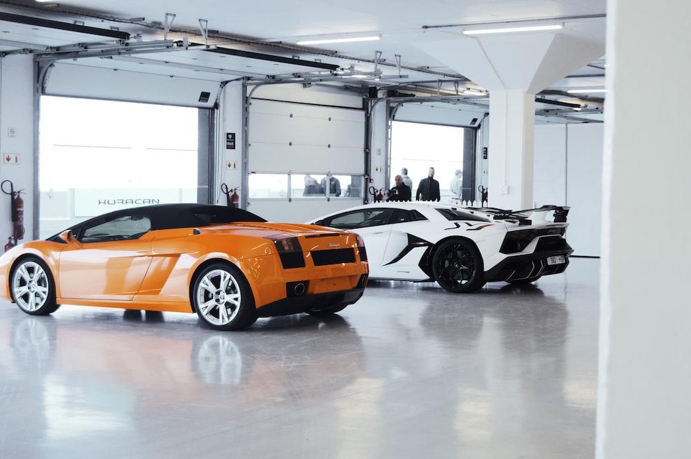 orange coupe parked beside white luxury car