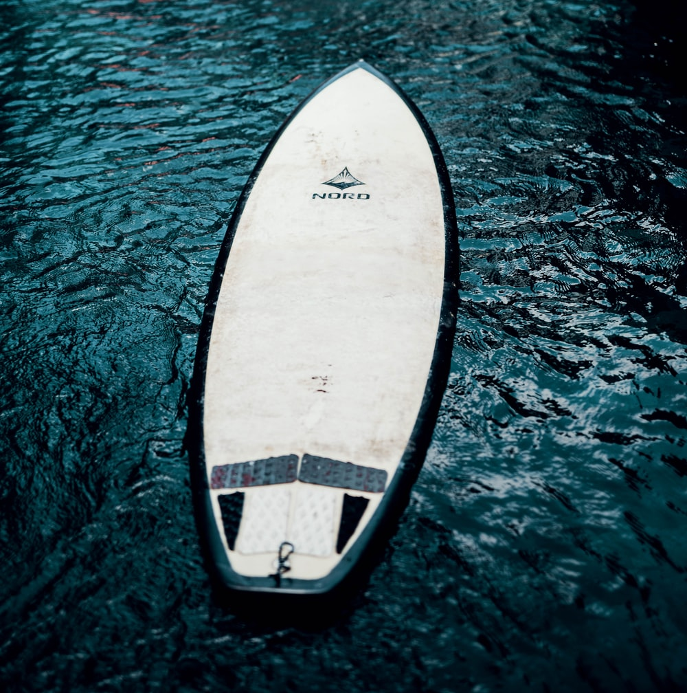 white and black surfboard on water