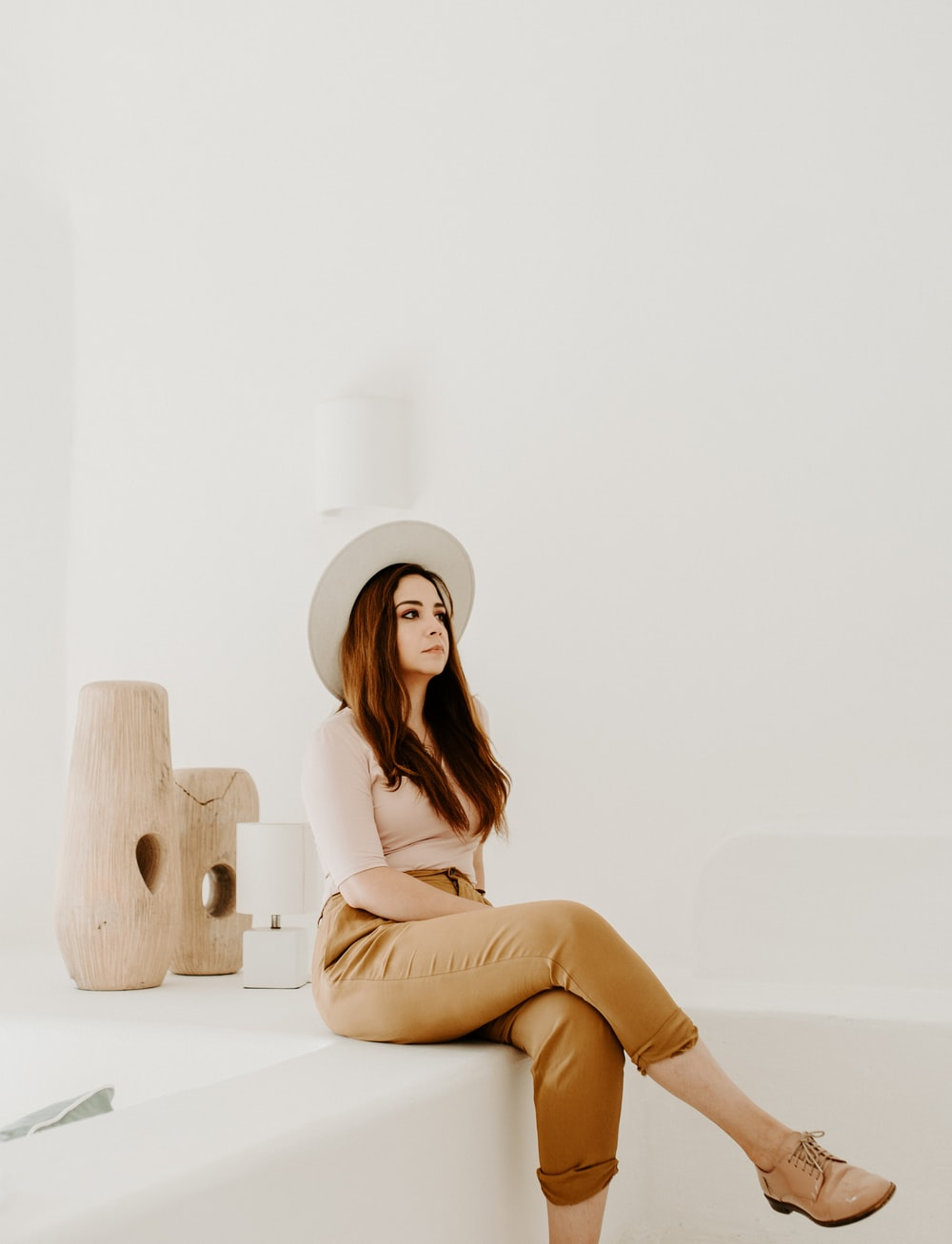 woman in beige crop-top sitting on white surface