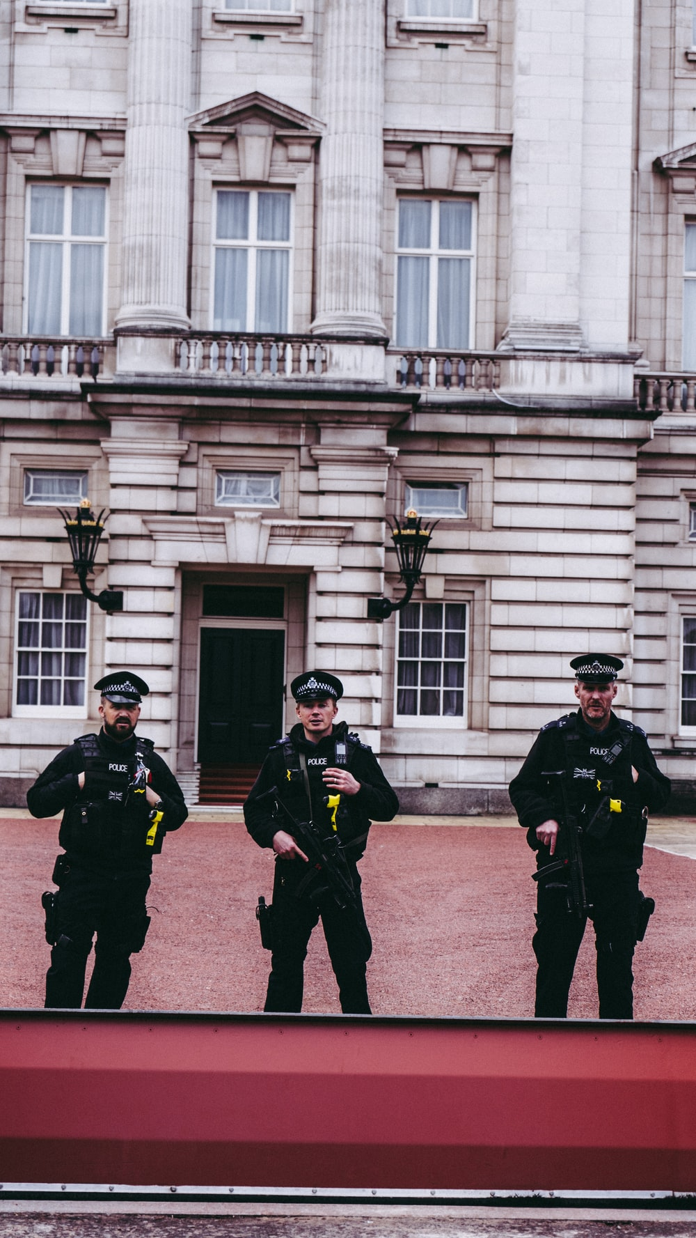 three police men standing in front of building