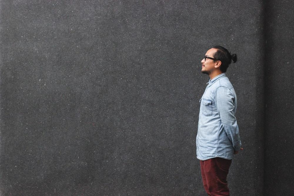 man in blue dress shirt standing beside wall