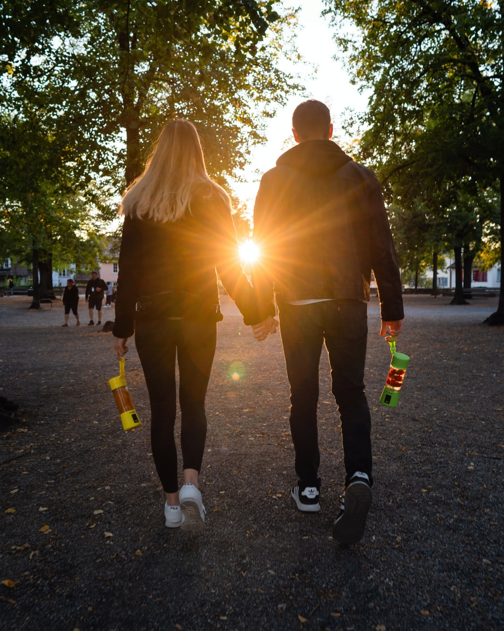 man and woman in black jacket walking on pathway near trees