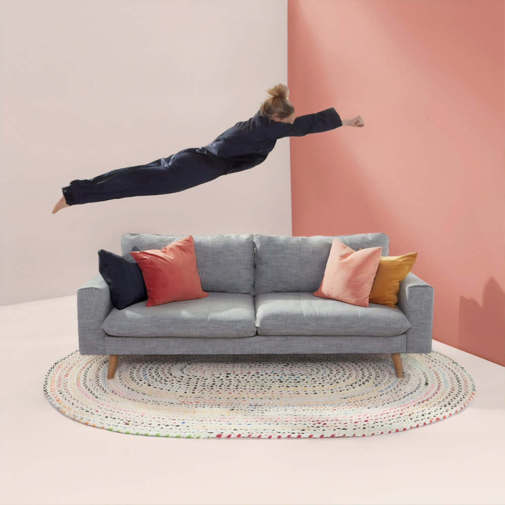 woman jumping in gray 2-seat sofa