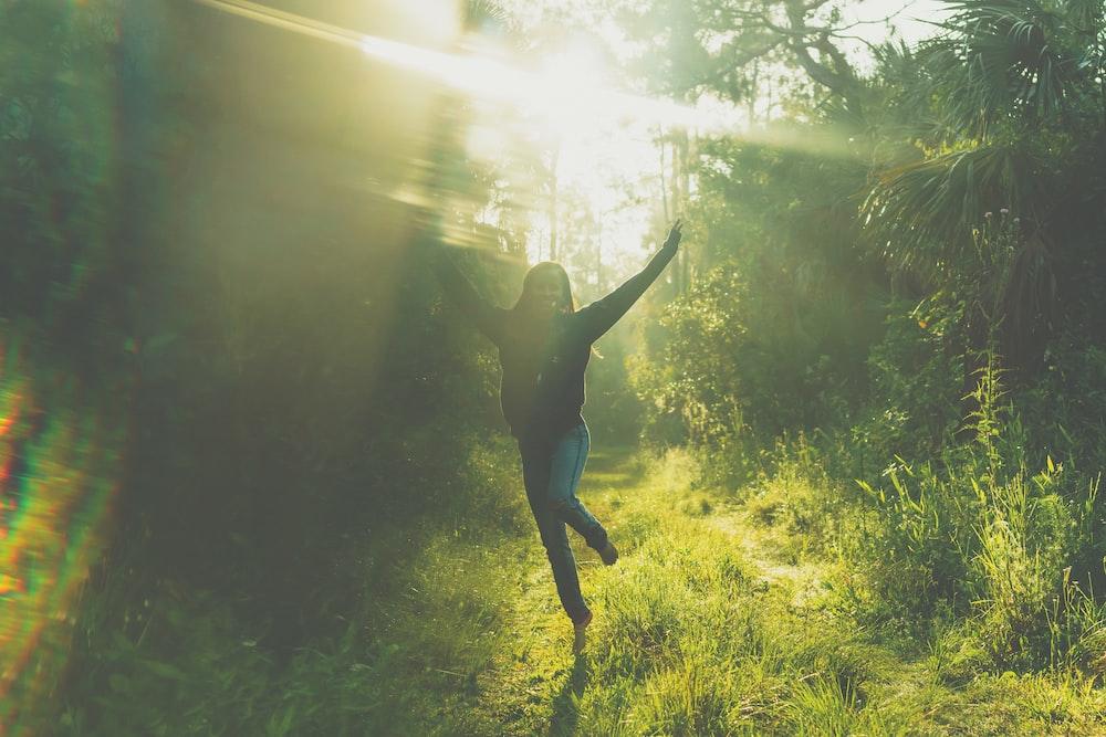 woman jumping near trees