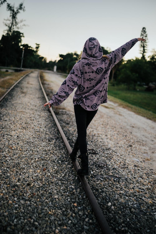 person wearing hoodie walking near road