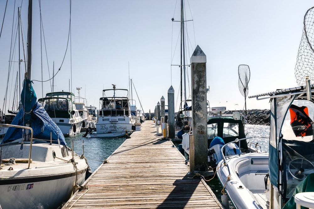 wooden dock between sailboats