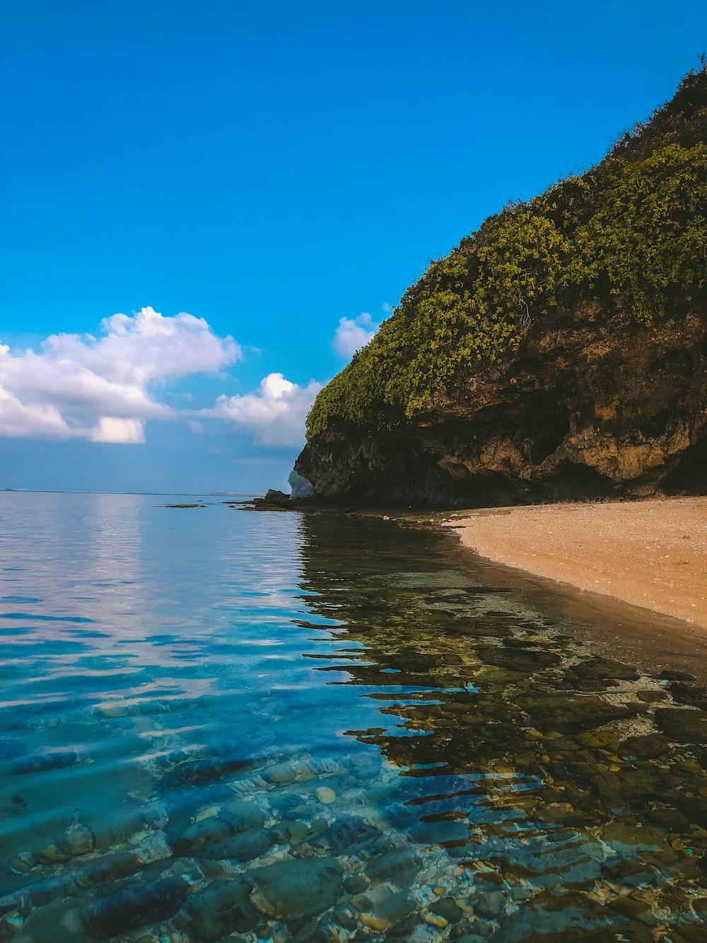 island and sea under blue sky