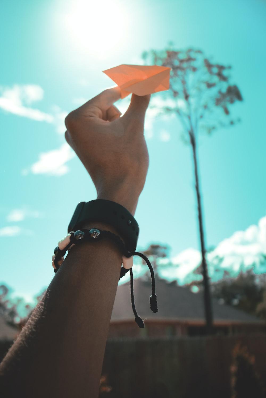 person holding orange paper plane toy