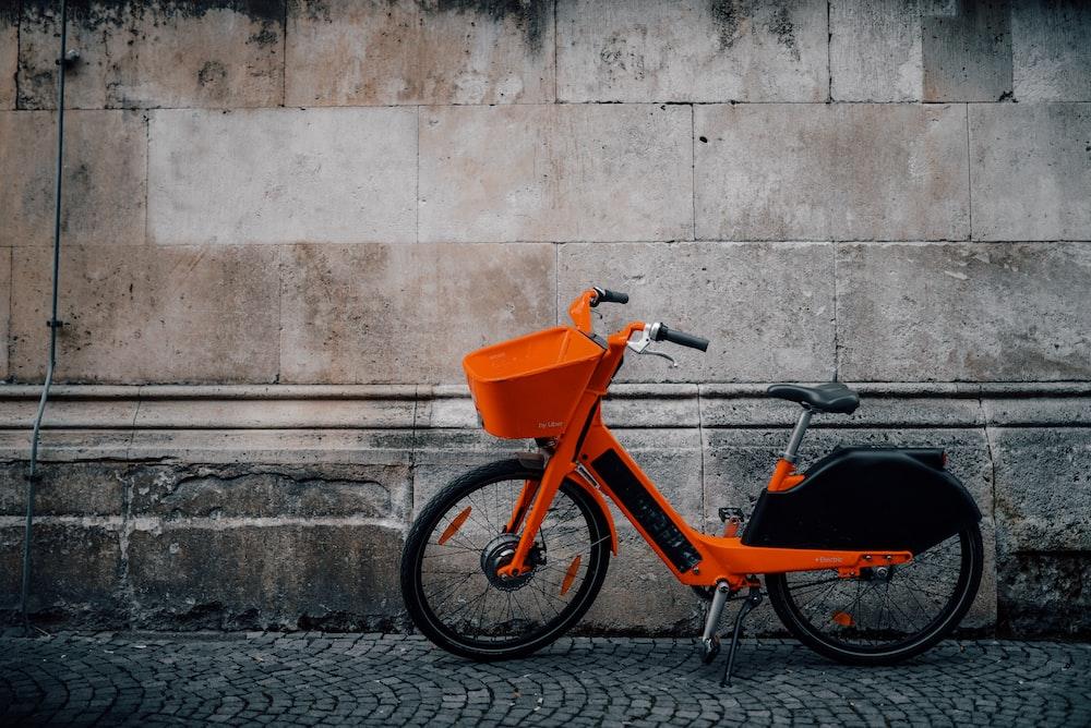 orange bike parked beside wall