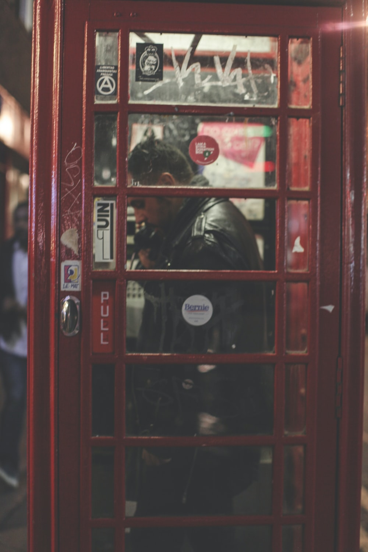 man inside telephone booth wearing black leather jacket