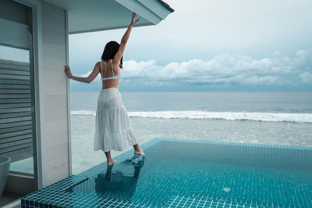 woman in white dress standing beside pool