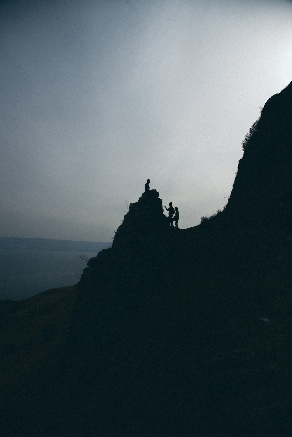 silhouette of people stand on mountain