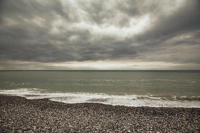 body of water under grey sky