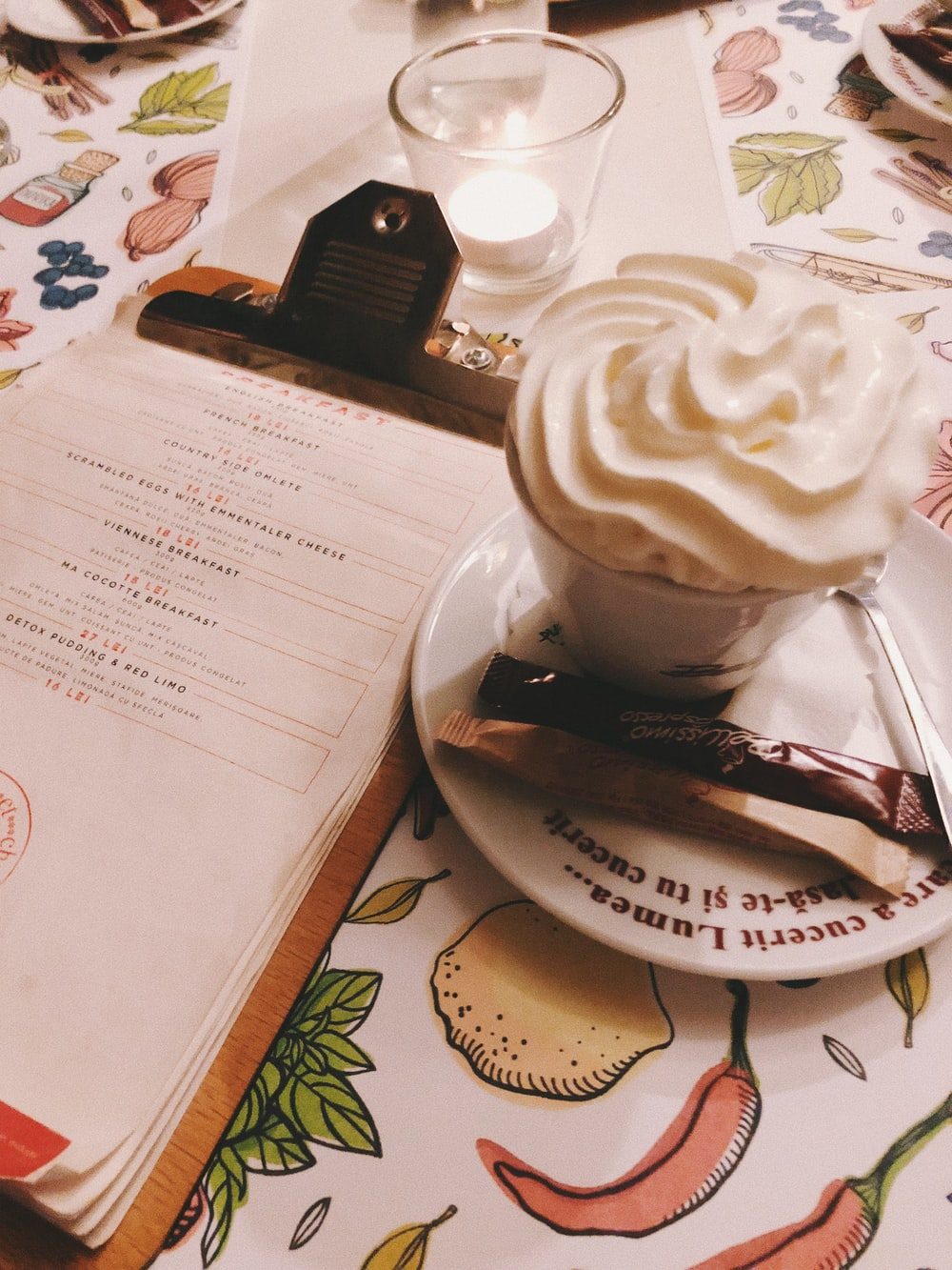 paper on clipboard beside cream in cup