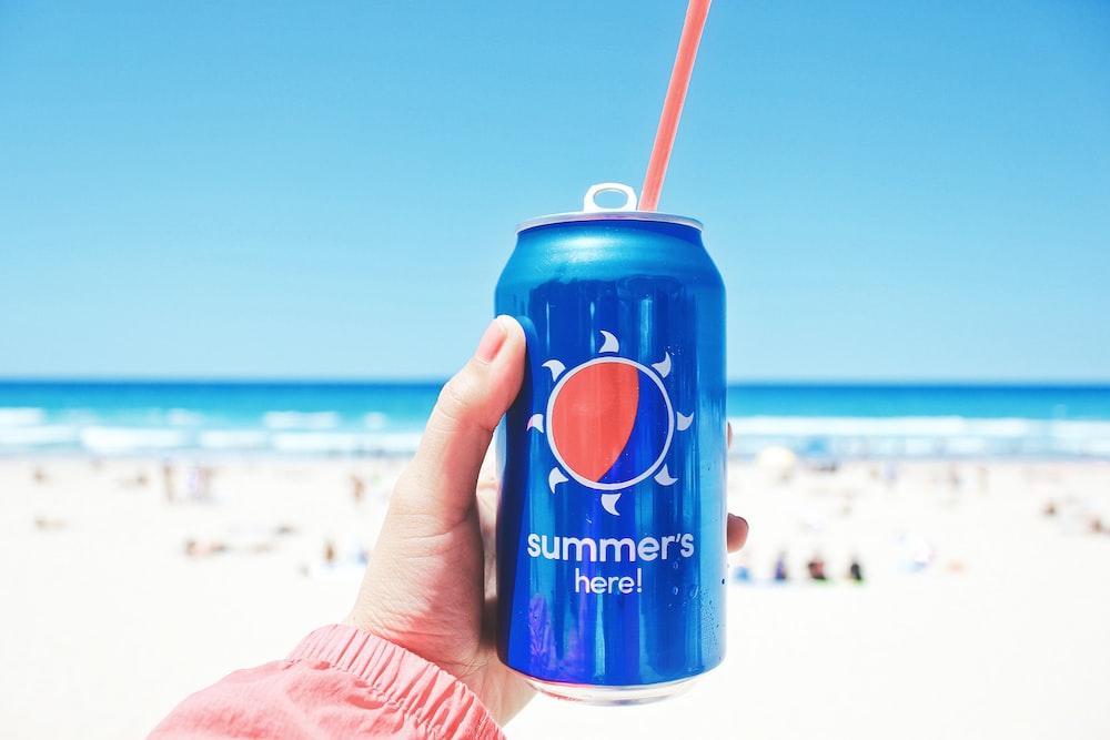 person holding Pepsi soda can on seashore