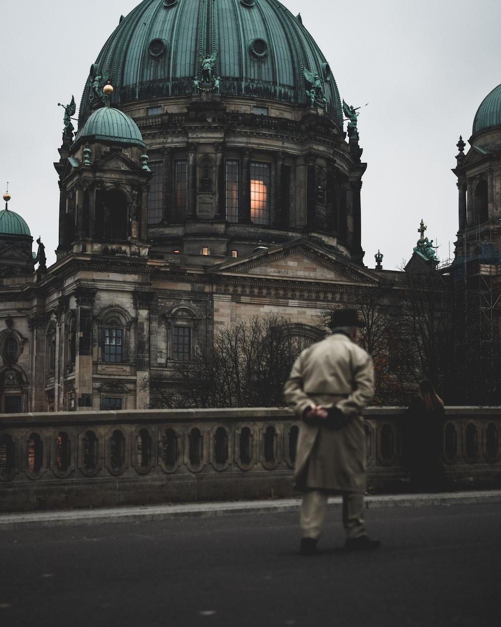 man walking on bridge near brown concrete dome building