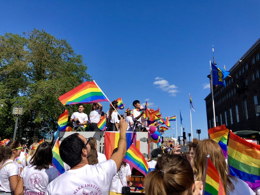 people holding multicolored flags
